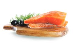 Pink smoked salmon on wooden plate with white cheese Stock Photos