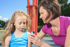 Mother using inhaler with her asthmatic daughter Stock Photos