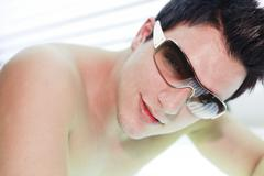 A man in a sunbath receiving high degree of ultraviolet light - stock photo