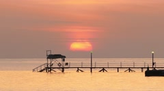 beautiful sunrise over pier in sea - telephoto lens, timelapse 4k - stock footage
