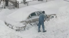 Man shovels snow from parked car - stock footage