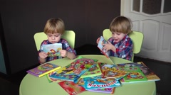 Stock Video Footage of Kids twins having fun looking at pictures in books for children