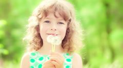 Happy child blowing dandelion in spring outdoors. Slow motion - stock footage