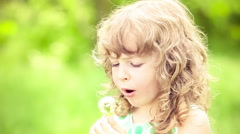 Stock Video Footage of Happy child blowing dandelion in spring outdoors. Slow motion
