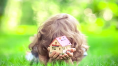Happy child holding model house in spring park. Slow motion Stock Footage