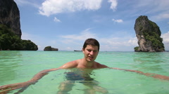 Guy stands in transparent azure sea and speaks Stock Footage