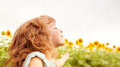 Happy child enjoying in spring sunflower field. Slow motion Stock Footage