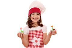 Happy little girl cook holding sweet muffin Stock Photos