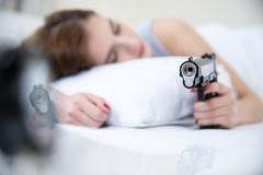 Woman in bed sleeps with hand on gun weapon home security. Focus on gun - stock photo