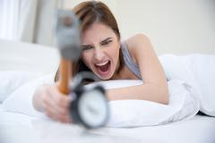 Woman not wanting to get up, taking a hammer to her alarm clock - stock photo