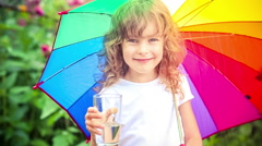 Happy child drinking water outdoors. Kid having fun in the rain. Slow motion Stock Footage