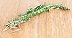 Rosemary branch on a chopping wooden board - stock photo