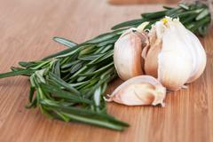 Rosemary and garlic on a wooden chopping board Stock Photos