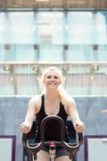 Young girl working out on stationary bicycle - stock photo