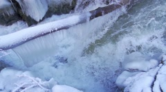 Mighty waterfall surrounded by icicles in winter in super slow motion Stock Footage