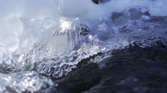 Creek in the mountains surrounded by melting ice in slow motion Stock Footage