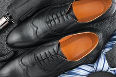 Classic men's shoes, tie, umbrella on the black leather Stock Photos