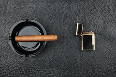 Lighter and black ashtray with cigar - stock photo
