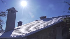 Roof of the house covered with snow,chimney smoke illuminated by the sun Stock Footage