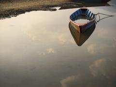 Rowboat Floating on Still Waters - stock photo