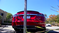 Traveling shot along the back of a Tesla electric car as it charges. Stock Footage