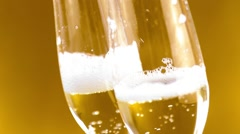 A pair of flutes of champagne with golden bubbles on golden background Stock Footage