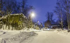 old wooden ruined barracks at winter night - stock photo