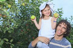 A girl and her daddy with apple background - stock photo