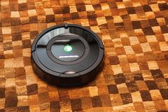 Robotic vacuum cleaner on carpet Stock Photos