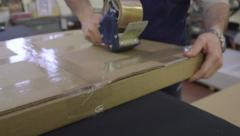 Employee taping box for shipping Stock Footage