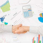 Business man working with financial data - shaking hands over contract Stock Photos