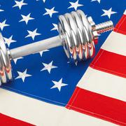Metal dumbbell over US flag as symbol of healthy nation - stock photo