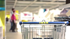 Ikea shopping cart stands in showroom with customers walking near, Russia Stock Footage