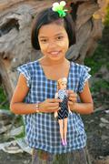 Young girl with thanaka paste on her face holding a doll, Amarapura, Myanmar Stock Photos