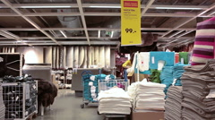 Staff in traditional yellow uniform of Ikea store works in showroom Stock Footage