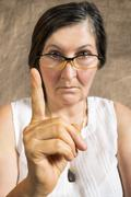 Stock Photo of Angry woman with finger pointing up