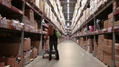 Caucasian woman walking along racks of self-service warehouse with freight cart Stock Footage