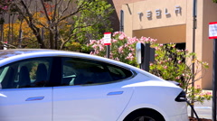 A Tesla electric car charging in front of Tesla corporate headquarters. Stock Footage