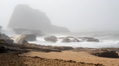 Time lapse of surf crashing on rocks and a beach. Mist fills the background Stock Footage