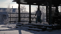 Shadows of people cleaning wooden porch from snow with shovel. Sunny winter day  Stock Footage