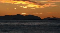 Golden sunset over mountain and fjord horizon on senja island Stock Footage