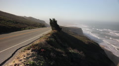 Footage of cars passing driving along Highway 1 in California next to the ocean Stock Footage