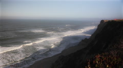 Waves of the Pacific Ocean crash on a beach at the bottom of cliffs on Highway 1 Stock Footage