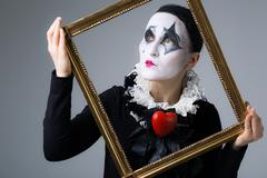 Woman in disguise harlequin in the picture frame Stock Photos