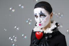 Woman in disguise harlequin with soap bubbles in the background - stock photo
