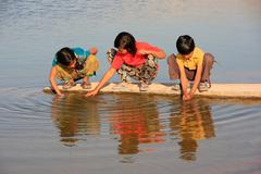 Local kids drinking from water reservoir, Khichan village, India - stock photo