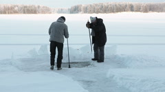 Adult man with crowbar and senior with an ax making ice-hoole for winter swim - stock footage