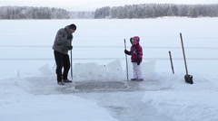 Adult man with crowbar and child with ax making ice-hoole for winter swimming - stock footage