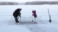Family making ice-hole for winter swimming, working with ax and crowbar - stock footage
