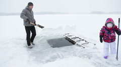 Young child helping father to maintain ice hole for winter swimming, frozen lake - stock footage